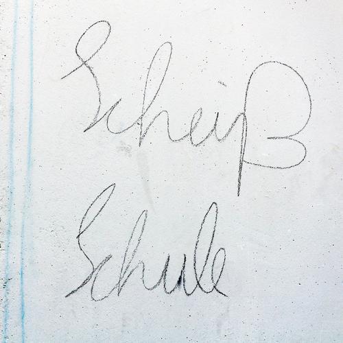 Schönschrift zählt auch Bildung Schule lernen Mauer Wand Schriftzeichen hell weiß Neid bequem Ärger Aggression Kommunizieren Schulkind Frustration