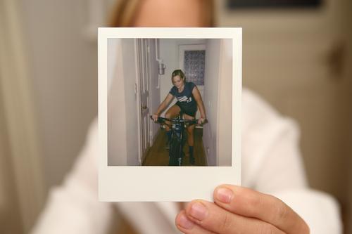 Frau hält Polaroidporträt von sich in die Kamera Stil Freude schön Leben Wohnung Sport Fahrradfahren Fotografie Sofortbildkamera Junge Frau Jugendliche