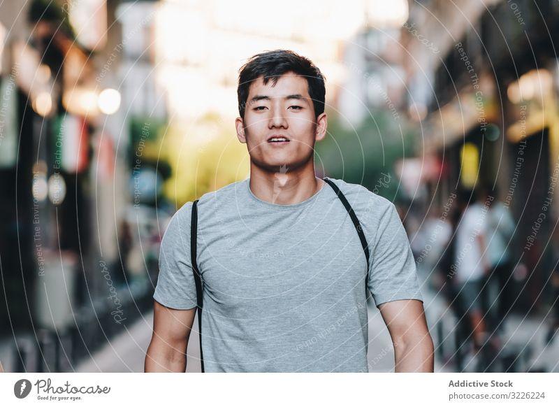 Selbstbewusster asiatischer Mann geht durch die Stadt selbstbewusst Straße Spaziergang Inhalt lässig T-Shirt gutaussehend urban schlendern Großstadt modern