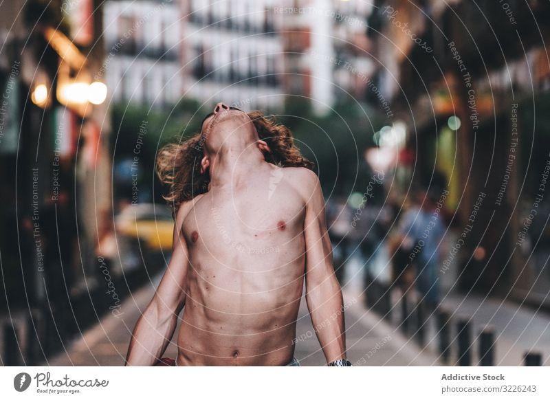 Sinnlicher Mann und Tanzen ohne Hemd auf der Straße sinnlich Starrer Blick selbstbewusst besinnlich nackt stehen gutaussehend urban lange Haare jung Erwachsener