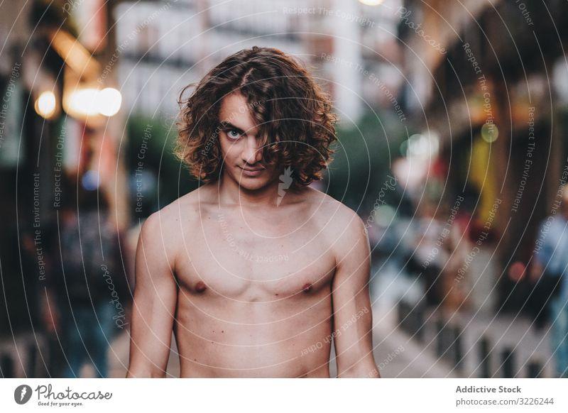 Sinnlicher Mann blickt und steht ohne Hemd auf der Straße sinnlich Starrer Blick selbstbewusst besinnlich nackt stehen gutaussehend urban lange Haare jung