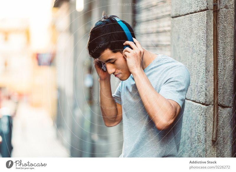 Mann mit Kopfhörern, der auf der Straße Musik hört Großstadt zuhören benutzend Streaming Inhalt cool freudig modern lässig stehen sonnig Stadt jung Erwachsener