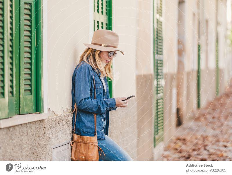Frau mit Smartphone lehnt an Steinhaus Glück schön sprechend attraktiv charmant Erholung Straße selbstbewusst Model Mitteilung nachdenklich Lächeln lieblich