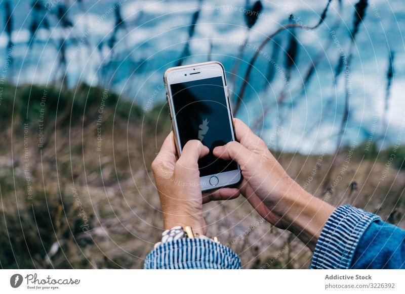 Person, die ein Smartphone benutzt, während sie an der Küste chillt reisen Seeküste MEER benutzend Drahtlos Touchscreen Nachrichtenübermittlung Apparatur Urlaub