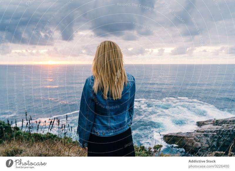 Frau am Meeresufer vor düsteren Wolken Horizont Meereslandschaft Sonnenuntergang Harmonie Kontemplation bedeckt Kälte malerisch Ausflug reisen ruhig
