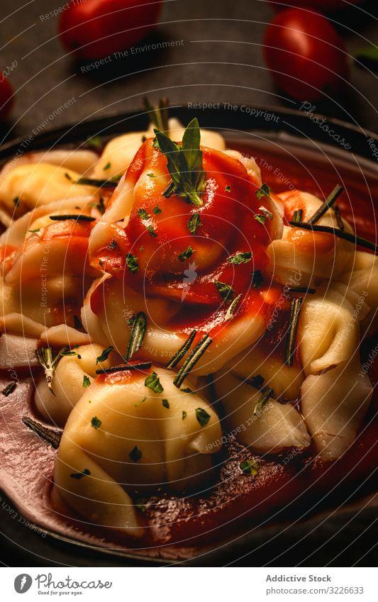 Platte mit köstlichen Ravioli mit Tomatensauce auf dem Tisch serviert Teller lecker Italienisch gekocht Kraut Feinschmecker Gabel Exquisit Serviette Rosmarin