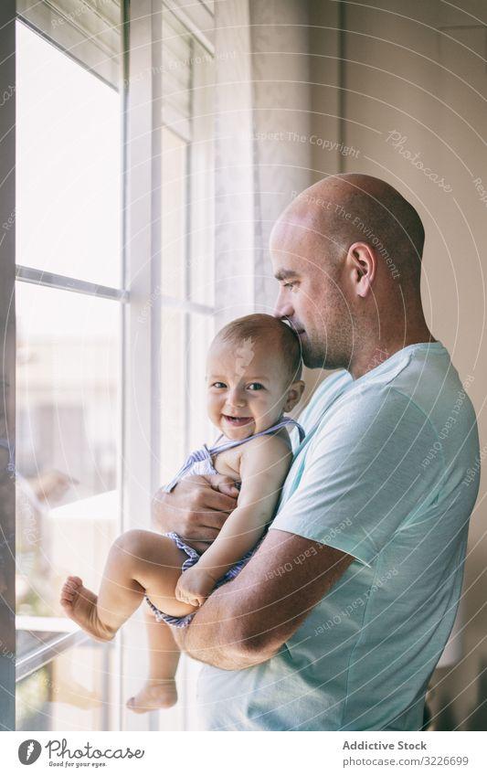 Vater mit Baby, der aus dem Fenster schaut Umarmung Kuss Glück gemütlich heimwärts Raum Familie Mann Kind Kleinkind Eltern Zusammensein Liebe Umarmen Pflege