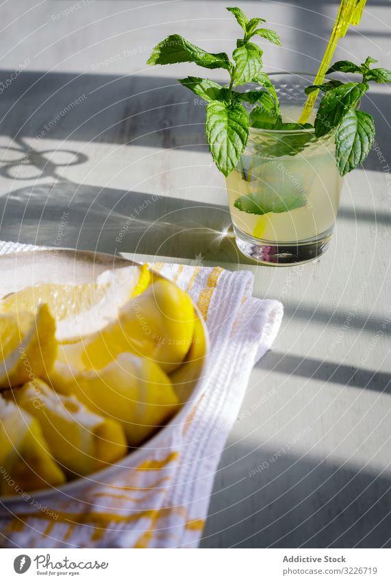 Glas frische Limonade neben dem Teller mit geschnittenen Zitronen auf dem Tisch Spielfigur Saft Küche hölzern rustikal selbstgemacht Minze Frucht trinken