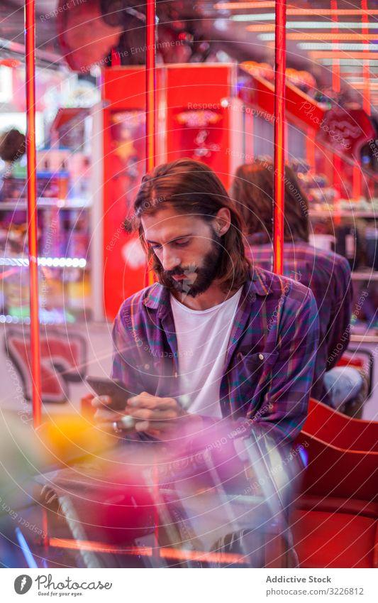 Fokussierter Hipster-Mann simst auf Smartphone, während er sich auf dem Rummelplatz ausruht Texten Messegelände ruhen Karneval fokussiert achtsam bärtig