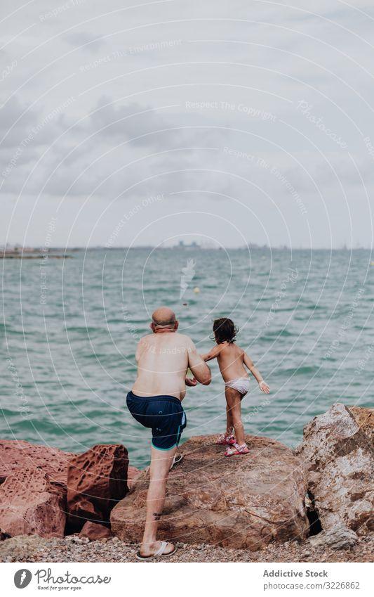 Grossvater und Enkelin amüsieren sich am felsigen Strand Urlaub Großvater Meer Familie älter Kind Mädchen Wasser Natur Ufer genießend in den Ruhestand getreten
