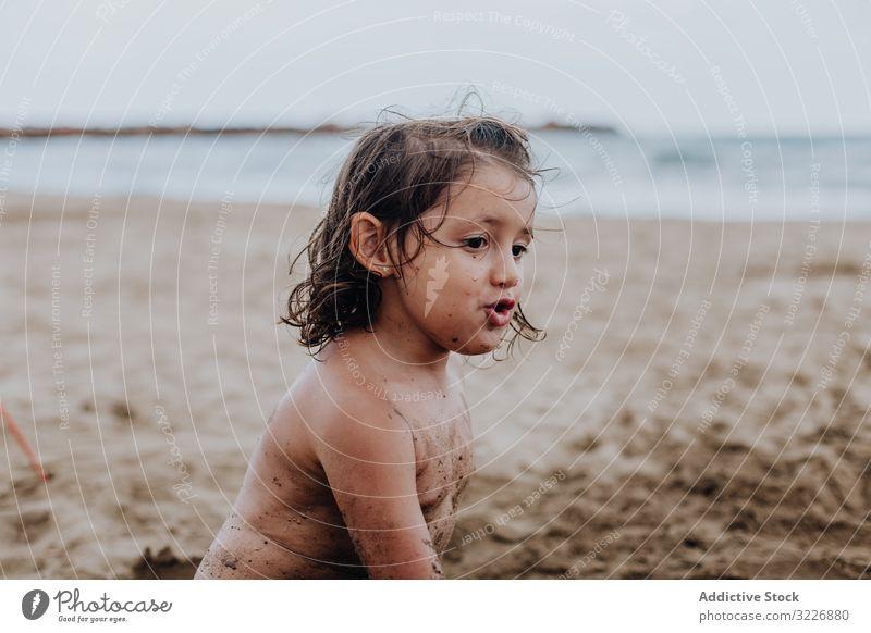 Inspiriertes Kind spielt mit Sand am Strand spielen Sommer Urlaub beschmiert Schürfen Feiertag Spaß Spielen Mund Mädchen Genuss Ausdruck Aktivität heiter