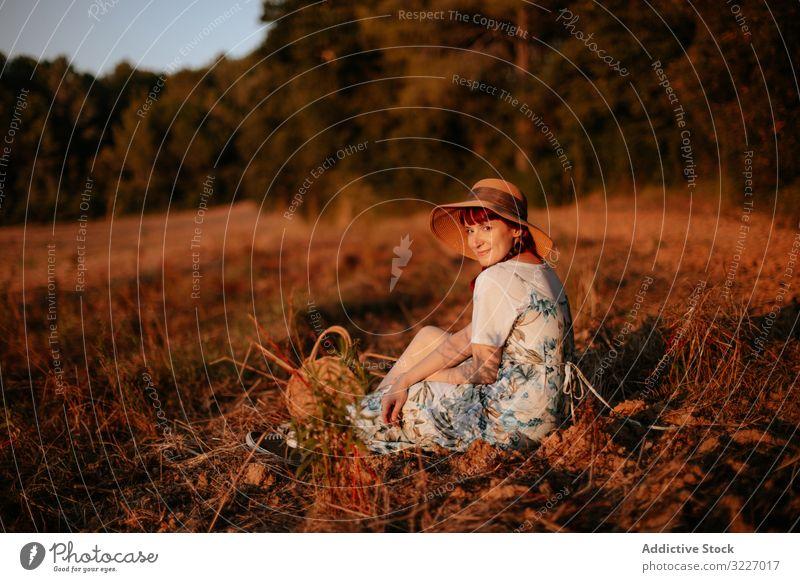 Frau auf dem Feld sitzend Sonnenuntergang retro Natur Abend Himmel Landschaft Lifestyle Sommer Wiese altehrwürdig Kleid Hut Harmonie idyllisch Windstille ruhig