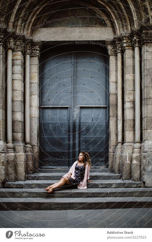Dame ruht in der Nähe einer Metalltür auf der Straße Tourist Tür Gebäude Frau alt sitzen Freitreppe Barcelona Spanien ruhen sich[Akk] entspannen Lifestyle