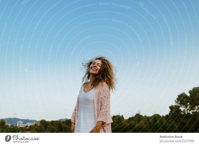 Glückliche Frau hebt die Arme in den Himmel geschlossene Augen Natur Freiheit Sommer Wochenende friedlich elegant Urlaub Freude sorgenfrei Windstille ruhig