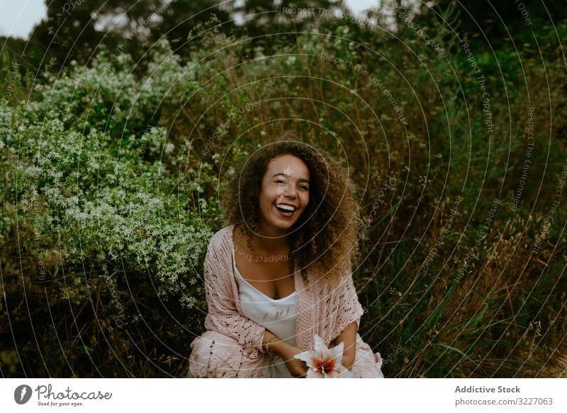 Lächelnde Frau berührt Blume im Wald Natur berühren Erwachsener elegant sinnlich Flora Pflanze Landschaft Botanik Wachstum Vegetation Harmonie idyllisch Dame