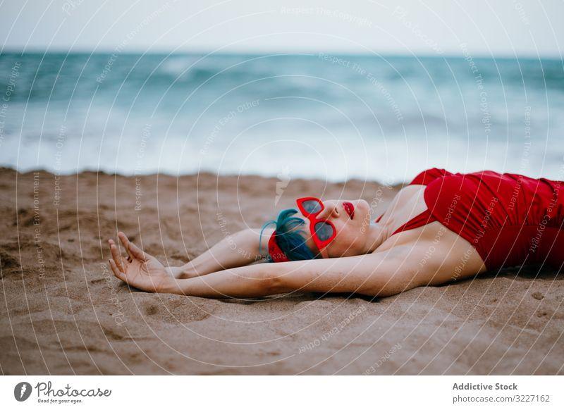 Entspannte Frau im hellen stilvollen Badeanzug am Sandstrand liegend Strand stylisch MEER retro Lügen Erwachsener sandig sinnlich Erholung Mode altehrwürdig