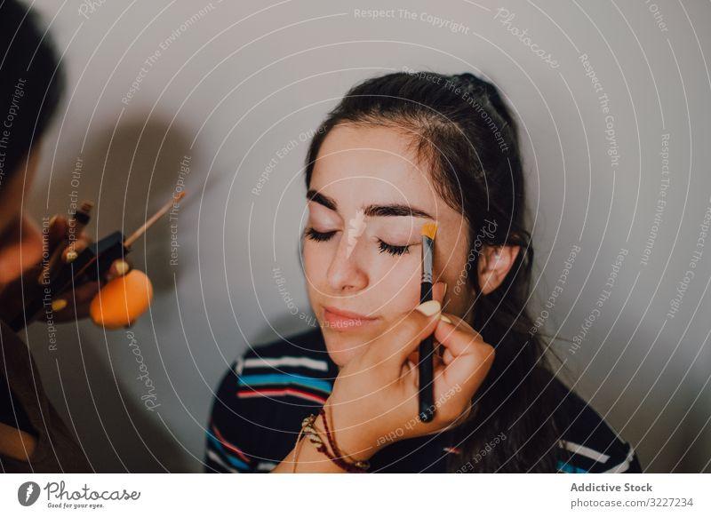 Junge Frau wird im Salon von Visagistin geschminkt Make-up visagiste Schönheit professionell Künstler Kosmetik Industrie Arbeit Beruf Gesicht jung Kunde Gerät