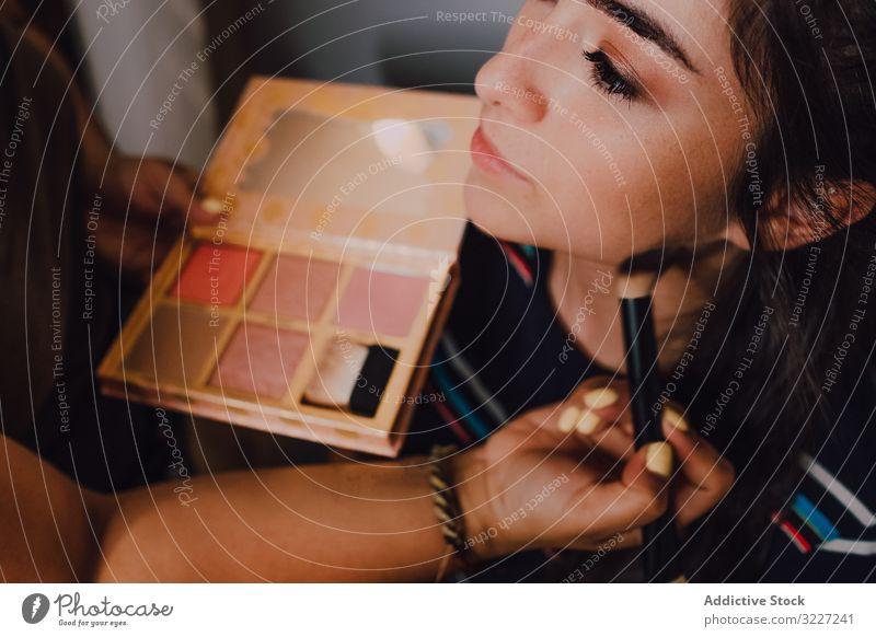 Attraktive junge Frau wird im Salon geschminkt Make-up visagiste Schönheit professionell Künstler Kosmetik Industrie Klient arbeiten Beruf Gesicht Kunde Gerät