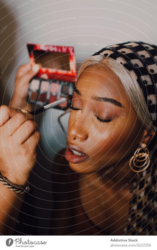 Afroamerikanische Frau wird im Studio geschminkt Make-up Lidschatten Schönheit professionell Künstler Kosmetik Industrie Klient Arbeit visagiste Beruf Gesicht