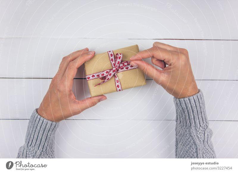 Frauenhand mit grauem Pullover als Eröffnungsgeschenk Geburtstag Schwarzer Freitag Schleife Feste & Feiern Weihnachten Textfreiraum Muttertag Freundschaft