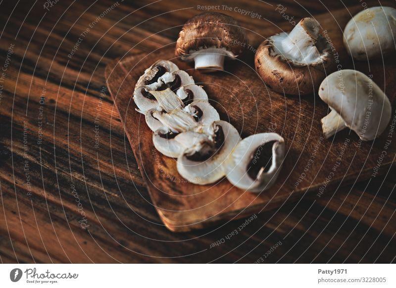 Champignons auf einem Schneidebrett aus Holz Lebensmittel Pilz Ernährung Bioprodukte Vegetarische Ernährung frisch lecker braun genießen Foodfotografie