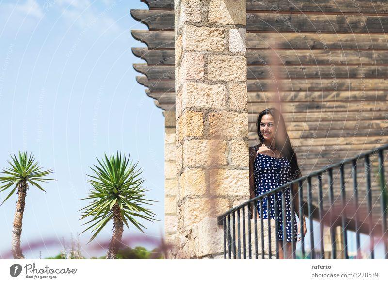 Schöne hispanische Frau in blauem Kleid, die sich an die Wand lehnt. Lifestyle Stil Glück schön Gesicht Sommer Mensch feminin Junge Frau Jugendliche Erwachsene