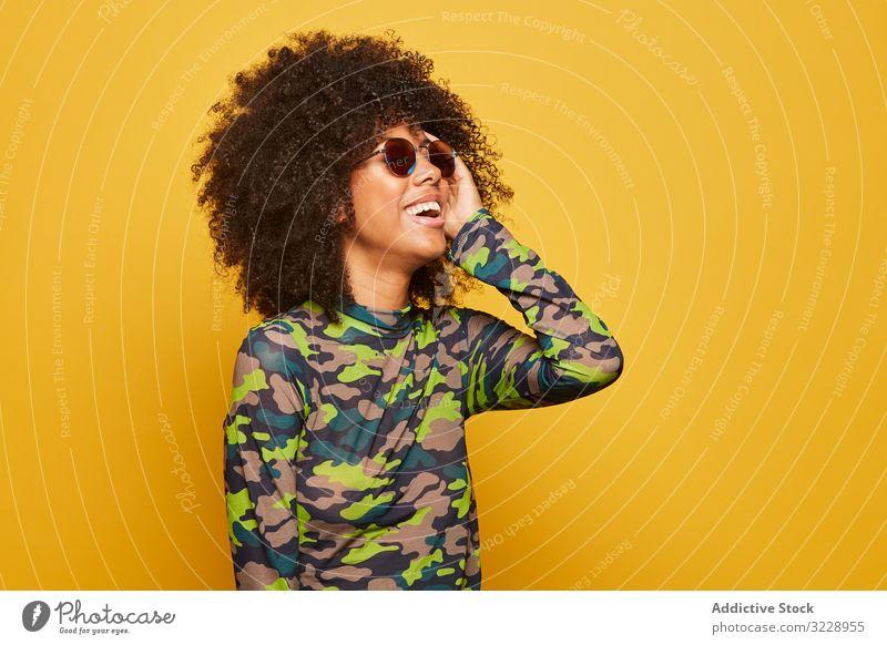Trendige ethnische Dame mit Sonnenbrille vor hellem Hintergrund Frau farbenfroh cool Afro-Look trendy pulsierend Glück lebhaft Outfit modern Hipster