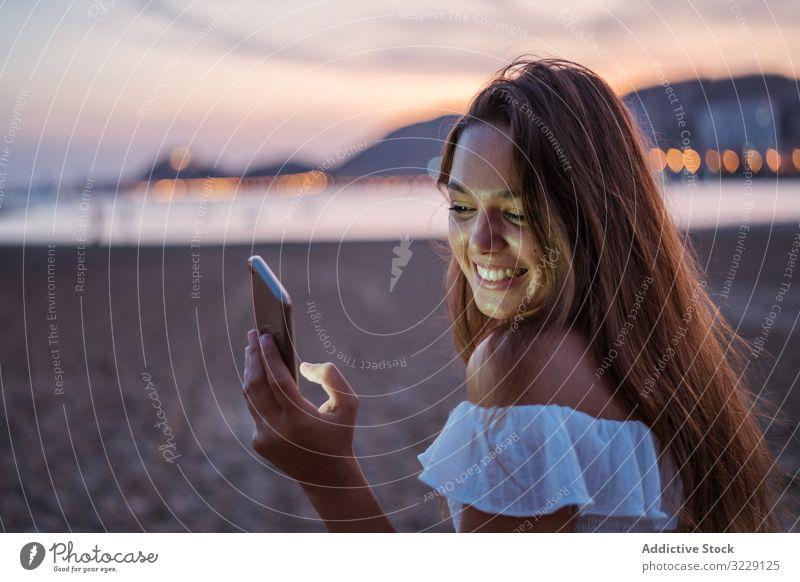 Fröhliche junge Frau benutzt Smartphone im Urlaubsort Strand benutzend soziale Netzwerke Lächeln Resort Abend Sommer Browsen Gerät Apparatur Mobile Telefon