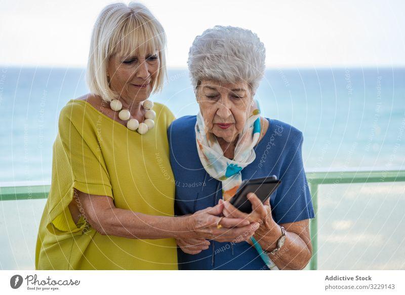 Ältere Damen mit Smartphone auf dem Hotelbalkon Frauen benutzend älter Freund Balkon MEER Resort soziale Netzwerke Senior reif Zusammensein Freundschaft Gerät
