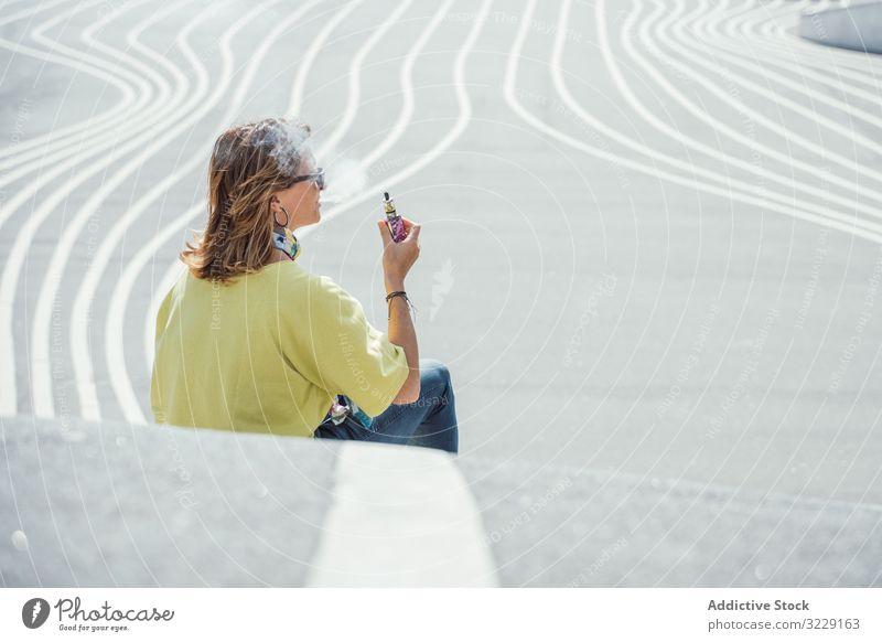 Moderne entspannte Frau, die auf markierter Straße sitzt vaping e Zigarette Rauch Verdunstung räkeln urban Sitzen Kälte Sonnenbrille farbenfroh Dampf Habitus