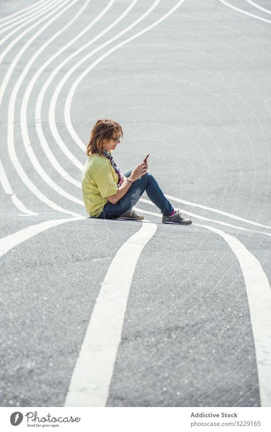 Moderne entspannte Frau auf markierter Straße und Smartphone urban Sitzen Sonnenbrille Erwachsener Asphalt ruhen Weg alternativ sorgenfrei Windstille modern