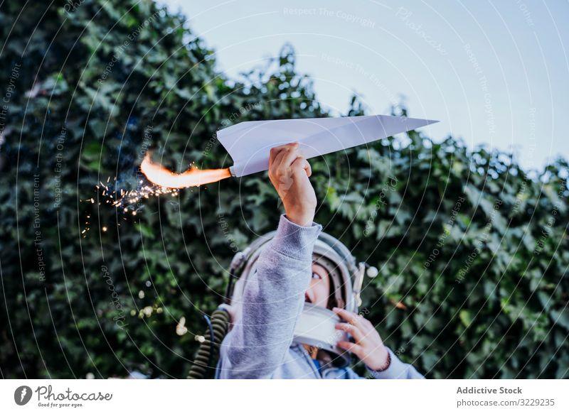 Überraschtes Kind hat Spaß mit funkelndem Flugzeug Junge spielen Ebene Spielzeug aufgeregt Papier petard überrascht Astronaut Schutzhelm Garten Glück Kindheit