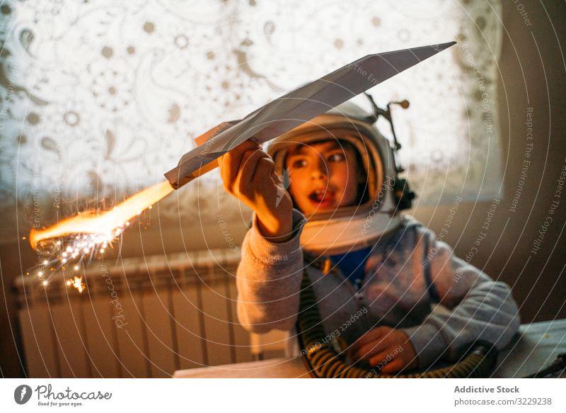 Verträumtes Kind hat Spaß mit Spielzeugflugzeug Junge spielen phantasieren Ebene Papier Flugzeug verträumt Astronaut Schutzhelm heimwärts Glück Kindheit