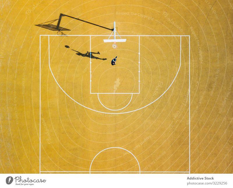 Junger Mann spielt Basketball auf einem Außenplatz. Athlet Konkurrenz Sportgerät Erwachsener Erholung Aktion Ball Porträt aktiv Aktivität Asphalt sportlich