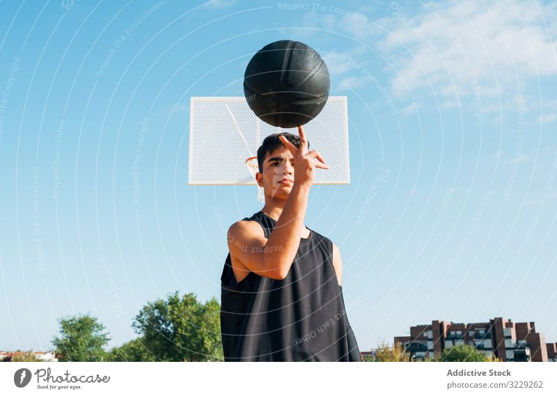 Junger Mann spielt auf gelbem Basketballfeld im Freien. Athlet Konkurrenz Sportgerät Erwachsener Erholung Aktion Ball Porträt aktiv Aktivität Asphalt sportlich