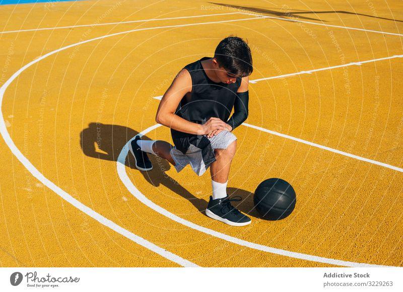 Junger Mann und Ball strecken sich auf dem Basketballfeld Athlet Konkurrenz Sportgerät Erwachsener Erholung Aktion aktiv Aktivität Asphalt sportlich Großstadt