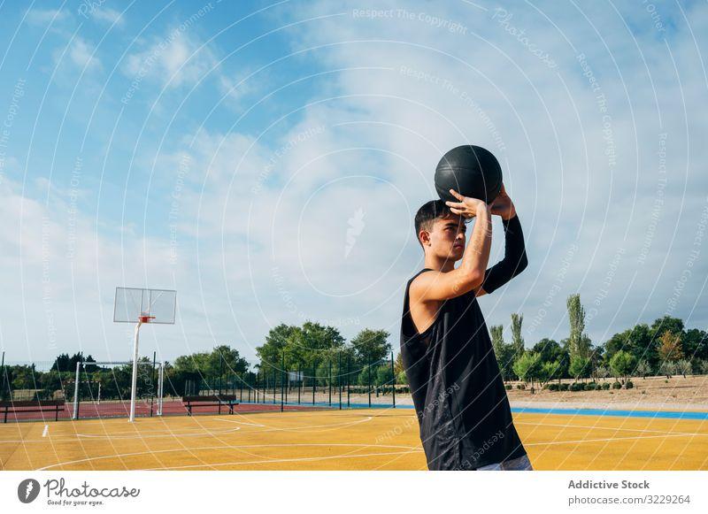 Junger Mann spielt auf einem Basketballplatz im Freien. Athlet Konkurrenz Sportgerät Erwachsener Erholung Aktion Ball Porträt aktiv Aktivität Asphalt sportlich