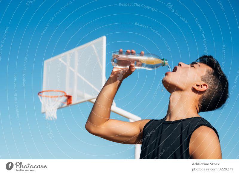Junger Mann spielt auf Basketballplatz im Freien Trinkwasser Athlet Konkurrenz Sportgerät Erwachsener Erholung Aktion Ball Porträt aktiv Aktivität Asphalt