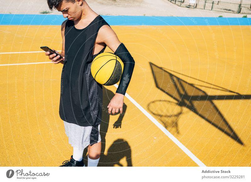 Männlicher Basketballspieler benutzt sein Smartphone nach dem Training in Ruhe Menschen im Freien Mann Großstadt Sport Straße urban jung Aktivität danach Ball