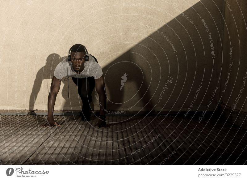 Ethnischer Sportler mit Kopfhörern macht sich zum Laufen bereit laufen Sprint Start Laufsteg ethnisch urban sportlich Training Sportbekleidung Ausdauer passen