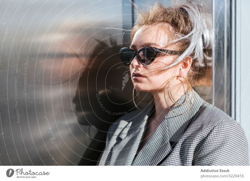 Stilvolle Frau mit schwarzer Sonnenbrille, die an einer Metallwand lehnt Mode Wand trendy Model urban Ohrringe altehrwürdig grau mollig retro Straße Dame Jacke