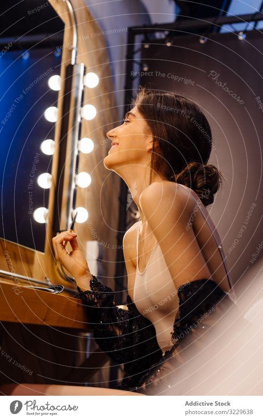 Brünette Frau schminkt sich vor dem Spiegel Make-up Model Schönheit Glamour Vorbereitung Schauspielerin Ankleidezimmer attraktiv hübsch brünett Frisur