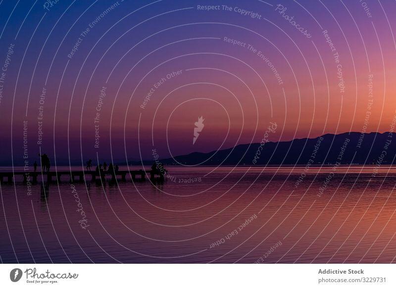 Sonnenuntergang auf einem Spazierweg am Meer mit Menschen Pier See Reisender Silhouette ruhig wolkenlos Himmel Abend hell Wasser Tourismus Ausflug Wochenende