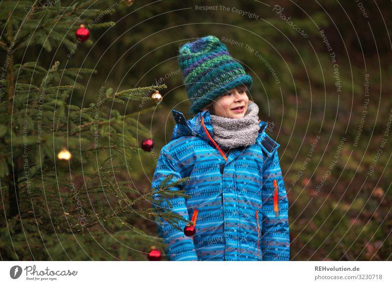 Kind steht an einem Weihnachtsbaum im Wald Vorderansicht Oberkörper Porträt Zentralperspektive Schwache Tiefenschärfe Unschärfe Tag Außenaufnahme Farbfoto
