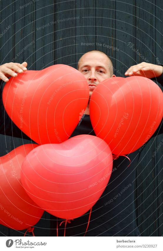 Herzenssache Feste & Feiern Mann Erwachsene 1 Mensch Mauer Wand Fassade Dekoration & Verzierung Luftballon Blick stehen rot schwarz Gefühle Stimmung Freude