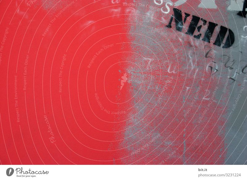 Schriftzug: Neid, steht gesprayt, gemalt in schwarzen Buchstaben, Typographie, Text, Wort auf einer roten Wand aus Stein, Beton eines Hauses geschrieben. Die alte Mauer der Stadt, ist beschmiert mit Graffiti von vielen Buchstaben.