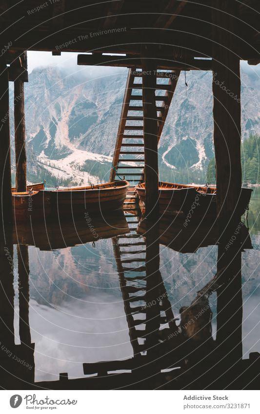 Vertäute Holzboote an der Mole am See in den Bergen Boot Wasser Dock Treppe Dolomiten Prahlerei Berge u. Gebirge Italien Tourismus tirol Europa Teich Pier Ruhe