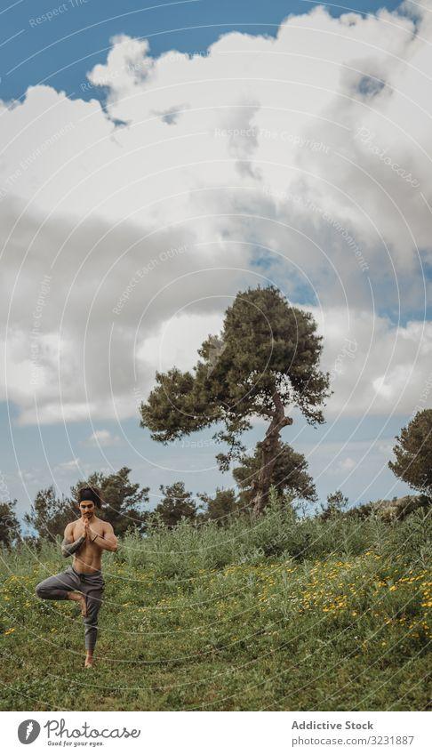 Mann trainiert Yoga auf der Wiese Asana Übung Energie Mediation Ausgeglichenheit Konzentration Dehnung Zen sich[Akk] entspannen Gleichgewicht Sport Lifestyle