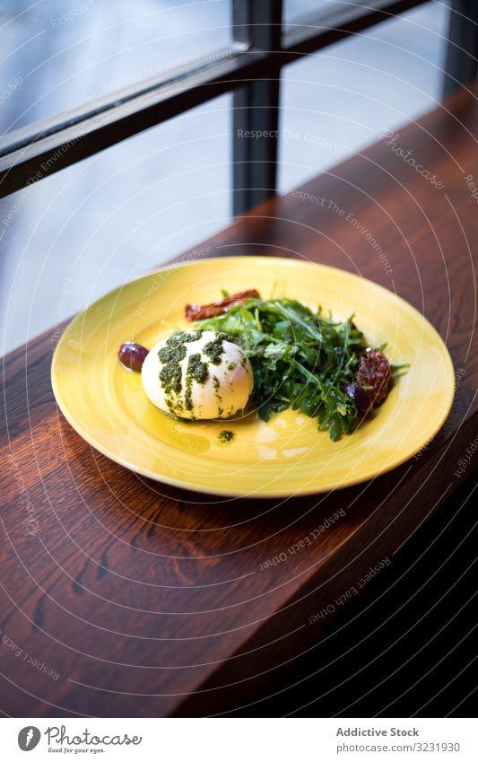 Gelber Teller mit gesundem Frühstück auf Holztheke Ei pochiert Grün Lebensmittel Café serviert Gesundheit lecker Mahlzeit Saucen Pesto Feinschmecker frisch