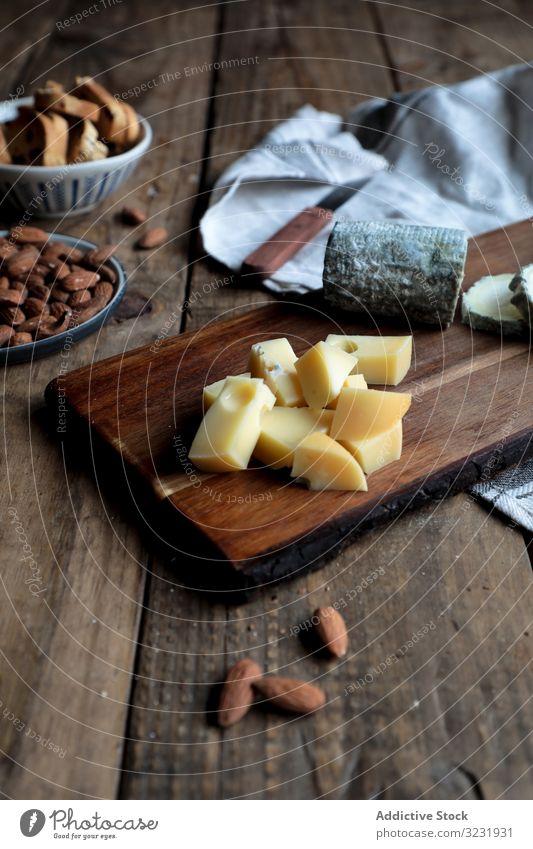 Croutons und Nüsse in Bretternähe mit Käse Holzplatte Tisch geschnitten Mandel Rosine Küche Lebensmittel hölzern Messer Brot Nut sortiert verschiedene Scheibe